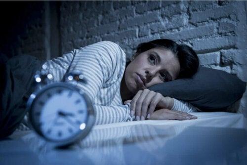 Kvinde, der ligger søvnløs i seng, oplever natteangst