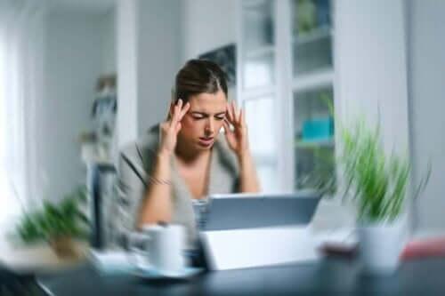 Kvinde ved computer har brug for øvelser til svimmelhed