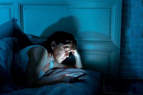 Kvinde med telefon i sengen