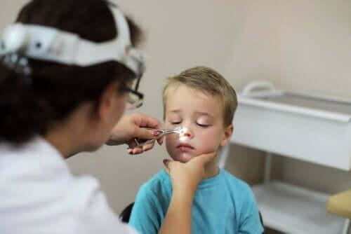 Læge tjekker drengs næse for adenoiditis