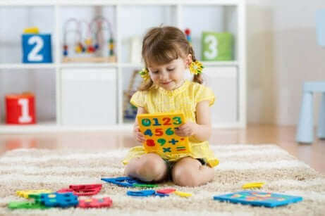 Lille pige leger med tal som eksempel på børn med autisme