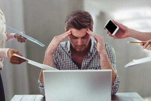 Stresset mand ved computer rækkes en masse ting