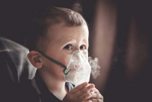 Barn med iltmaske på