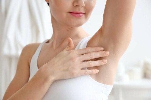 Kvinde tager sig til armhule