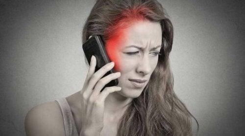 Kvinde, der får hovedpine af at snakke i telefon