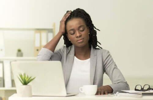Kvinde ved skrivebord har hovedpine