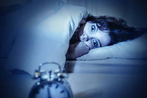 Søvnløs kvinde i seng oplever søvnparalyse