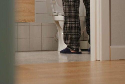 Mand står foran toilet