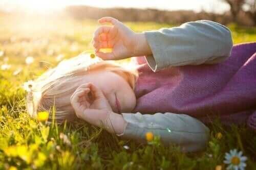 Barn, der ligger på græsplæne