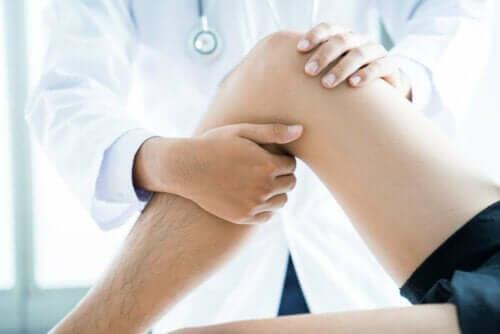 Læge behandler mands ben som symbol for Eden Hazards skade