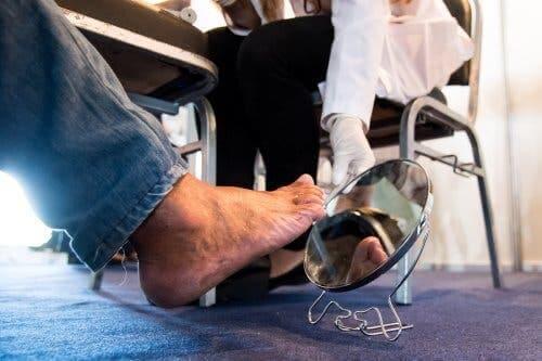 Læge tjekker diabetisk patients fod med spejl