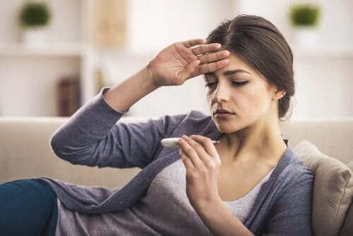 Kvinde med feber tager sig til panden