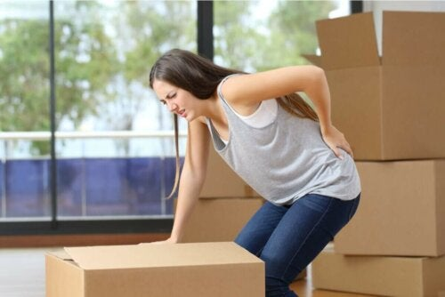 Kvinde med flyttekasser har ondt i ryggen