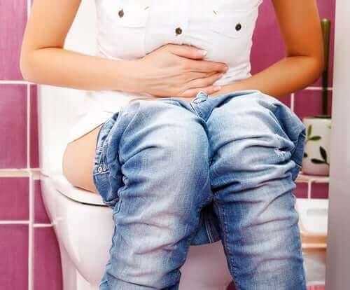 Kvinde på toilettet holder sig for maven