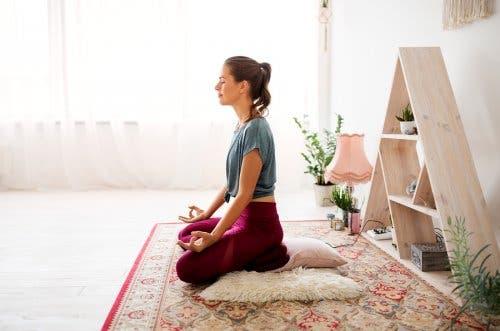 Kvinde mediterer indenfor for at bekæmpe udmattethed fra psoriasisgigt