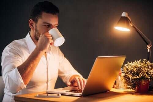 Mand arbejder hjemmefra med kaffe i hånden