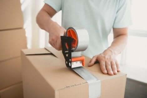 Mand lukker papkasse med tape