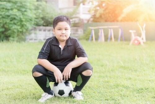 Dreng, der sidder på fodbold, symboliserer gode vaner hos børn