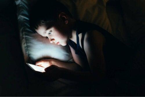 Dreng ligger med telefon i mørke i sengen