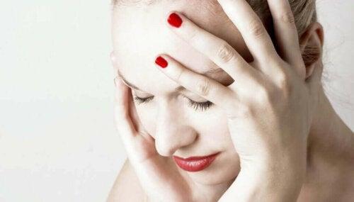 Kvinde med hovedpine tager sig til hoved