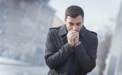 Mand fryser og holder hænderne op til munden