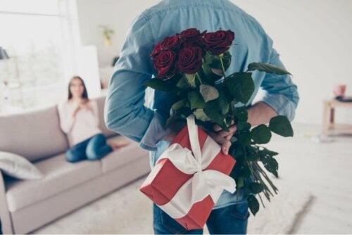 Mand overrasker kvinde med blomster og gave som et af de gængse kærlighedssprog