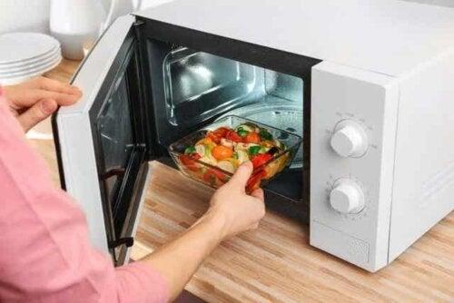 Person, der skal til at opvarme mad i mikrobølgeovn