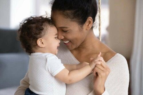 Smilende mor med baby i armene