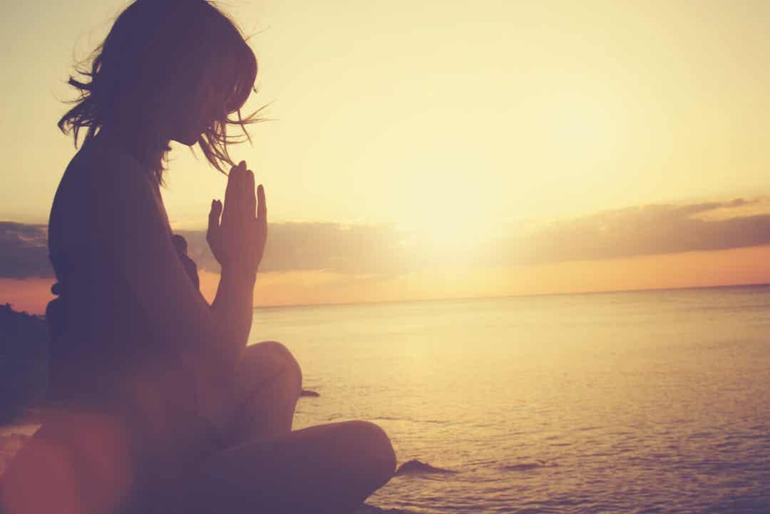 Kvinde mediterer ved vand for at leve mere bevidst