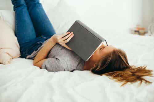 Kvinde læser i bog i sengen