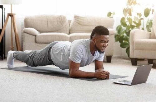 En mand, der træner derhjemme med en bærbar computer