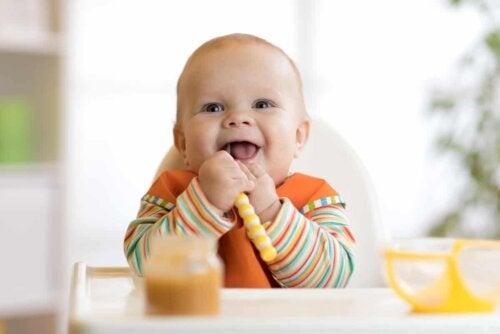 En glad baby spiser kommerciel babymad