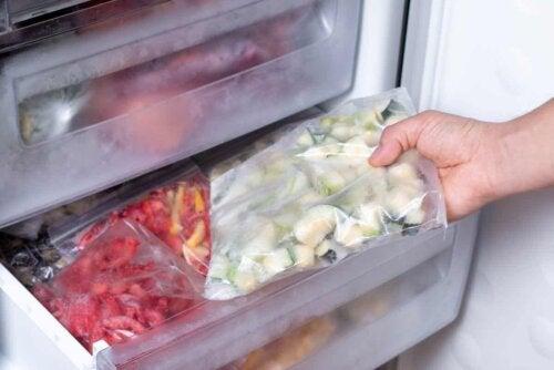 Person er ved at fryse grøntsager skåret i stykker