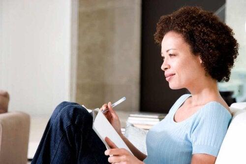Kvinde skriver i bog