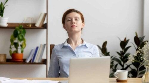 Kvinde foran computer hviler øjnene