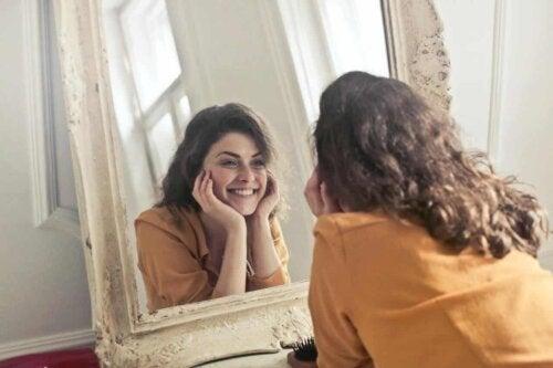 Kvinde smiler til sig selv i spejlet